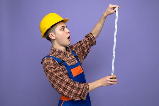 Verrast jonge mannelijke bouwer dragen uniform uitrekkende meetlint