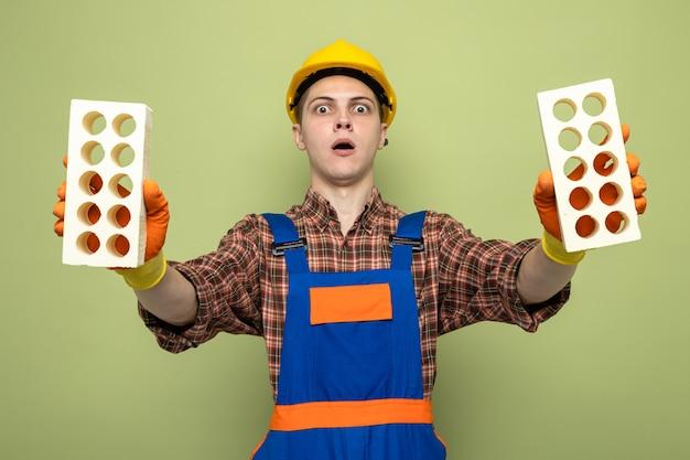 Verrast jonge mannelijke bouwer uniform dragen met handschoenen met bakstenen?