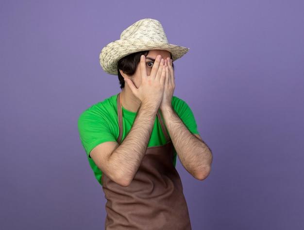 Verrast jonge mannelijke tuinman in uniform dragen tuinieren hoed bedekt gezicht met handen