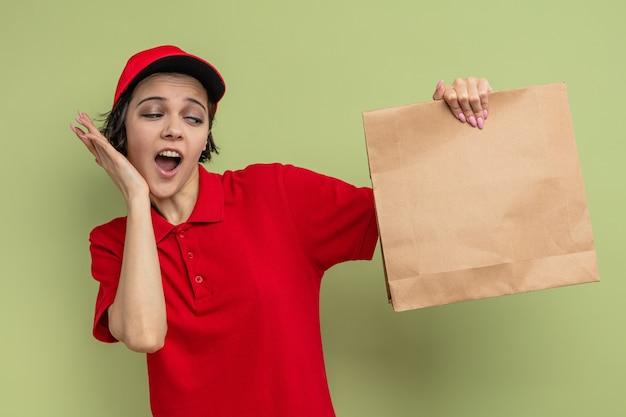Verrast jonge, mooie bezorger die haar hand op haar gezicht legt en papieren voedselverpakkingen vasthoudt
