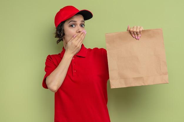 Verrast jonge, mooie bezorger die haar hand op haar mond legt en papieren voedselverpakkingen vasthoudt