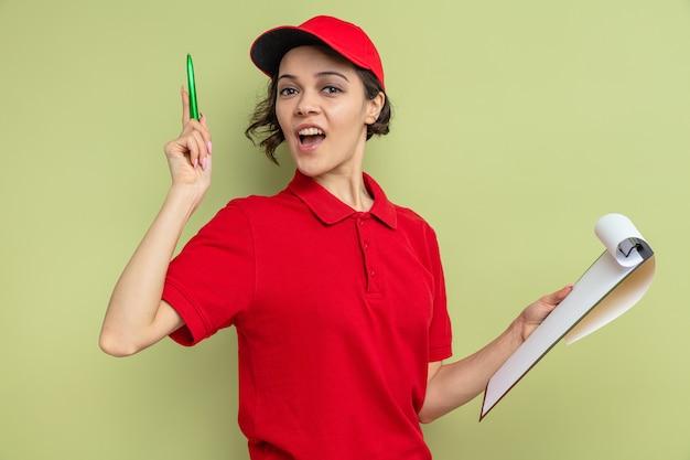 Verrast jonge, mooie bezorger die klembord vasthoudt en omhoog wijst met pen