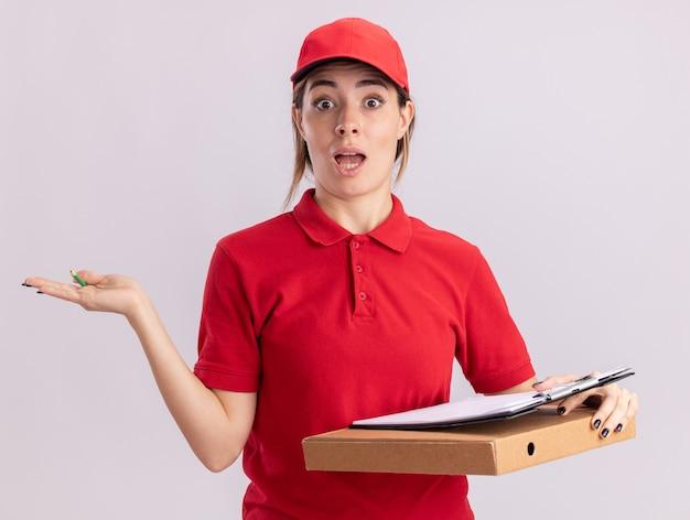 Verrast jonge mooie bezorger in uniform houdt de hand open en houdt klembord op pizzadoos geïsoleerd op een witte muur
