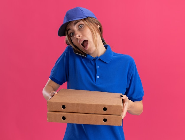 Verrast jonge mooie bezorger in uniform houdt pizzadozen en praat over telefoon op roze
