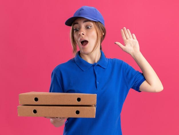 Verrast jonge mooie bezorger in uniform staat met opgeheven hand en houdt pizzadozen op roze