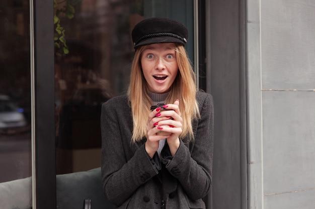 Verrast jonge mooie blonde vrouw in modieuze kleding ogen afronden tijdens het kijken, poseren over groot raam buiten met papieren beker in opgeheven handen