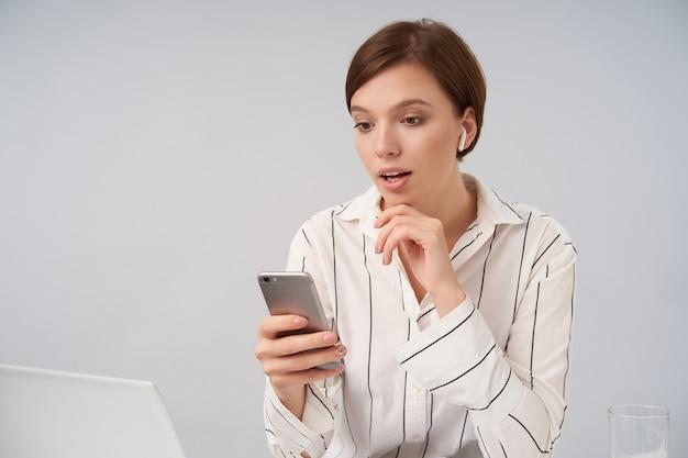 Verrast jonge mooie bruinharige vrouw met kort trendy kapsel verbaasd kijken naar het scherm van haar mobiele telefoon en met opgeheven hand onder haar kin, geïsoleerd op wit
