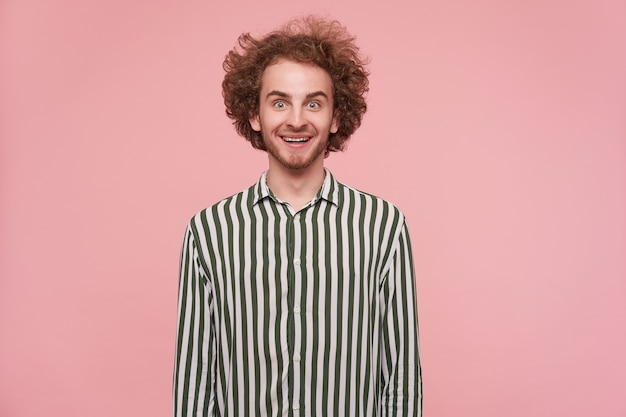 Verrast jonge mooie roodharige man met baard rond zijn groene ogen terwijl hij verbaasd naar de camera kijkt en vrolijk lacht, geïsoleerd over roze muur in vrijetijdskleding