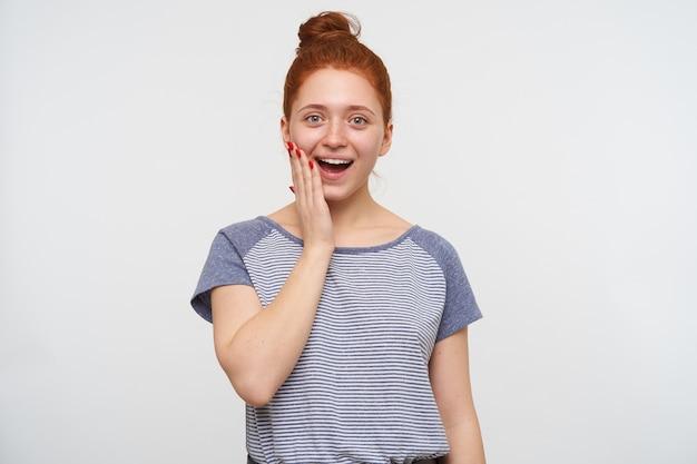 Verrast jonge mooie roodharige vrouw met knot kapsel met opgeheven palm op haar wang en opgewonden kijkend, staande tegen een witte muur