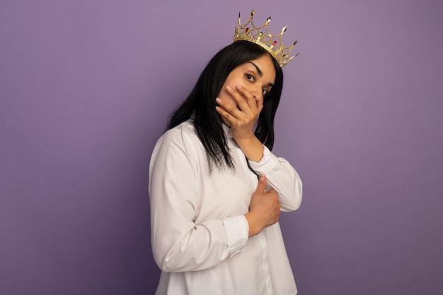 Verrast jonge mooie vrouw, gekleed in wit t-shirt en kroon bedekt mond met hand
