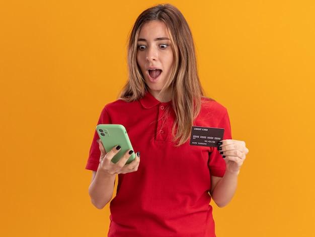 Verrast jonge mooie vrouw houdt creditcard en kijkt naar telefoon geïsoleerd op oranje muur