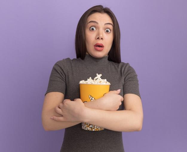 Verrast jonge mooie vrouw knuffelen emmer popcorn geïsoleerd op paarse muur
