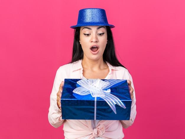 Verrast jonge, mooie vrouw met een feesthoed die vasthoudt en kijkt naar een geschenkdoos geïsoleerd op een roze muur