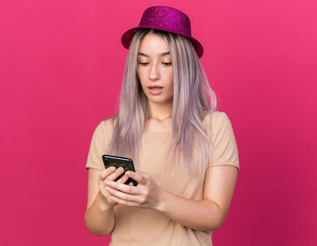 Verrast jonge, mooie vrouw met een feesthoed die vasthoudt en naar een telefoon kijkt die op een roze muur is geïsoleerd