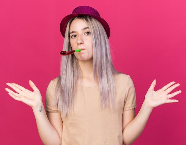 Verrast jonge mooie vrouw met feestmuts blazende feestfluitje verspreiden handen geïsoleerd op roze muur