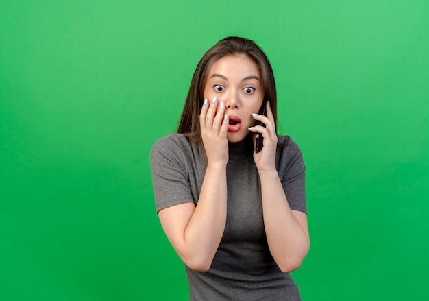 Verrast jonge mooie vrouw op zoek rechtstreeks praten aan de telefoon aanraken gezicht geïsoleerd op groene achtergrond met kopie ruimte