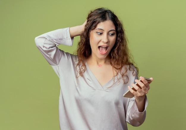 Verrast jonge mooie vrouwelijke kantoormedewerker houden en kijken naar telefoon en hand zetten achter hoofd geïsoleerd op olijfgroene muur