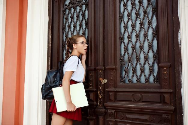 Verrast jonge mooie vrouwelijke student permanent in de buurt van oude houten deur, afluisteren.