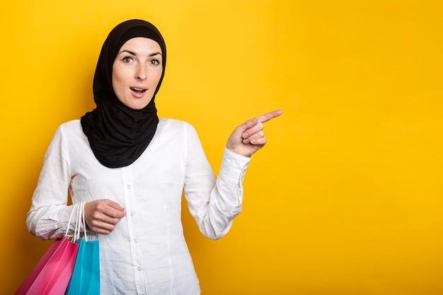 Verrast jonge moslimvrouw in hijab houdt boodschappentassen vast en wijst met de vinger opzij tegen geel