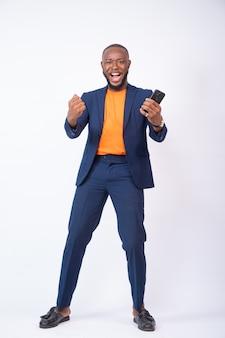 Verrast jonge nigeriaanse zakenman vieren terwijl hij naar zijn telefoon kijkt