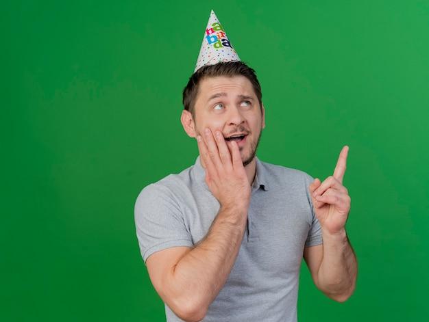 Verrast jonge partij kerel dragen verjaardag glb zetten hand op wang punten omhoog geïsoleerd op groen