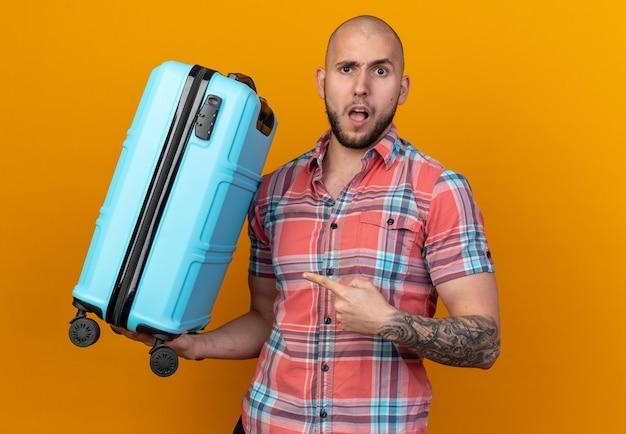 Verrast jonge reiziger man houden en wijzend op koffer geïsoleerd op oranje muur met kopieerruimte