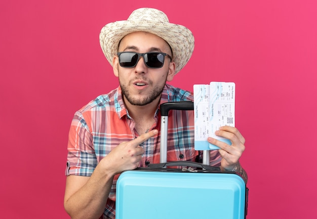 Verrast jonge reiziger man met stro strand hoed in zonnebril houden en wijzend op vliegtickets staan achter koffer geïsoleerd op roze muur met kopie ruimte