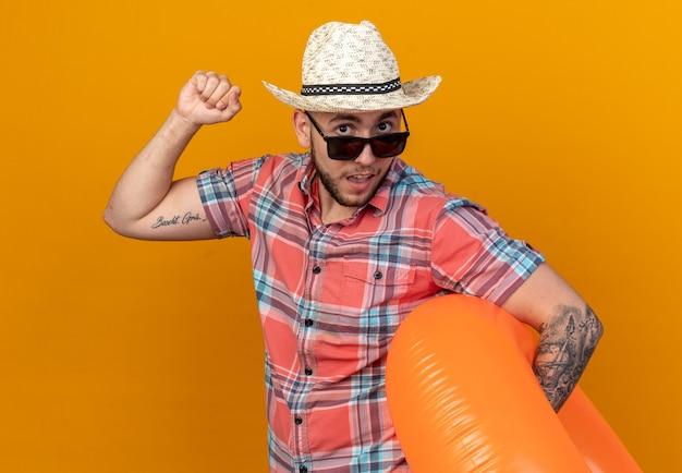 Verrast jonge reiziger man met stro strand hoed in zonnebril met zwemring en staande met opgeheven vuist geïsoleerd op oranje muur met kopie ruimte