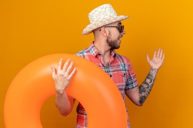 Verrast jonge reiziger man met stro strand hoed in zonnebril met zwemring kijkend naar kant geïsoleerd op oranje muur met kopie ruimte