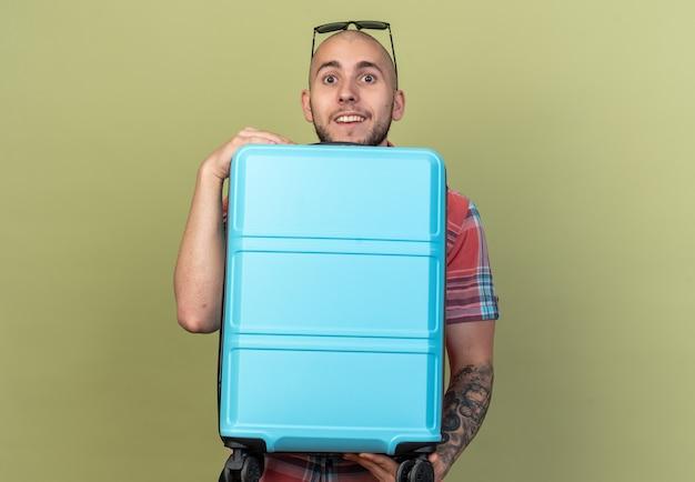 Verrast jonge reiziger man met zonnebril met koffer geïsoleerd op olijfgroene muur met kopieerruimte