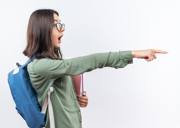 Verrast jonge schoolvrouw die een bril draagt met een rugzak die boeken aan de zijkant vasthoudt