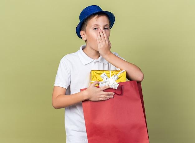 Verrast jonge slavische jongen met blauwe feestmuts hand op de mond zetten en geschenkdoos in boodschappentas houden geïsoleerd op olijfgroene muur met kopie ruimte