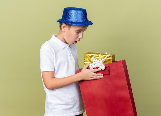 Verrast jonge slavische jongen met blauwe feestmuts houden en kijken naar geschenkdoos in boodschappentas geïsoleerd op olijfgroene muur met kopie ruimte