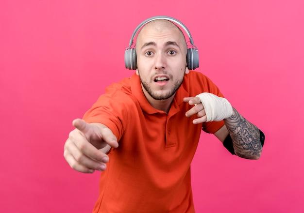Verrast jonge sportieve man met polsbandage hoofdtelefoon met telefoonarmband en punten geïsoleerd op roze muur dragen