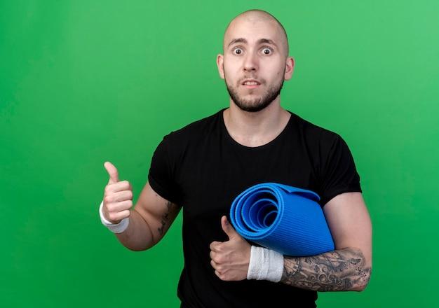 Verrast jonge sportieve man met polsbandje met yoga mat zijn duimen omhoog geïsoleerd op groene muur