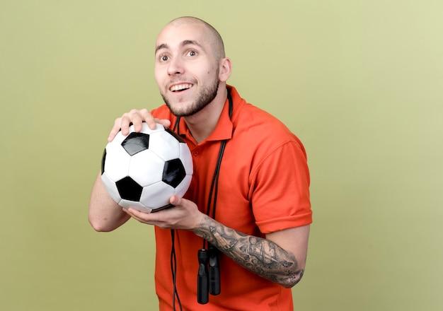 Verrast jonge sportieve man met springtouw op schouder en bal geïsoleerd op olijfgroene muur te houden