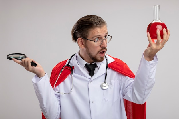 Verrast jonge superheld man medische gewaad met stethoscoop en bril holding vergrootglas en kijken naar chemie glazen fles gevuld met rode vloeistof in zijn hand geïsoleerd op witte achtergrond