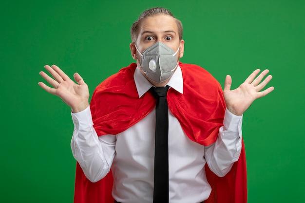 Verrast jonge superheld man met medische masker en stropdas spreidende handen geïsoleerd op een groene achtergrond