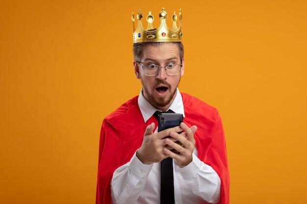 Verrast jonge superheld man met stropdas en kroon met bril houden en kijken naar telefoon geïsoleerd op een oranje achtergrond