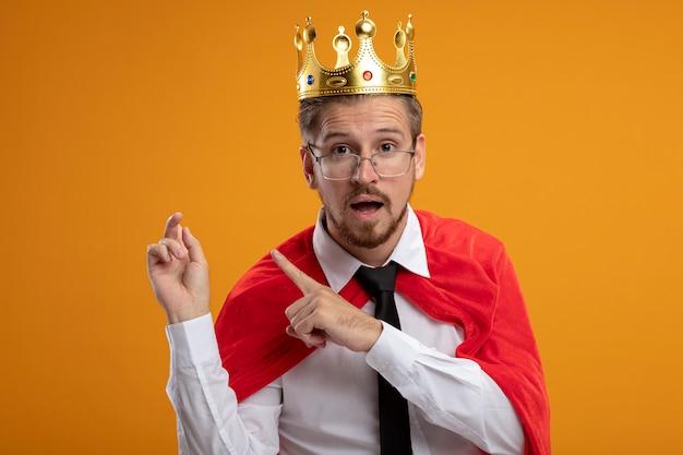 Verrast jonge superheld man met stropdas en kroon met glazen wijst op rug geïsoleerd op een oranje achtergrond met kopie ruimte