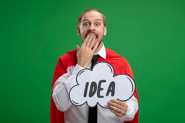Verrast jonge superheld man met stropdas idee bel houden en bedekte mond met hand geïsoleerd op groene achtergrond