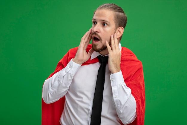 Verrast jonge superheld man stropdas dragen handen op wangen geïsoleerd op groen