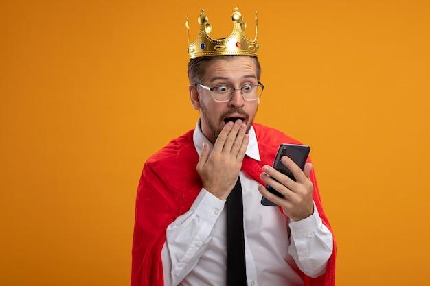 Verrast jonge superheld man stropdas en kroon met bril houden en kijken naar telefoon bedekt mond met hand geïsoleerd op een oranje achtergrond