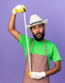 Verrast jonge tuinman afro-amerikaanse man met tuinhoed die zich uitstrekt over yape maatregel