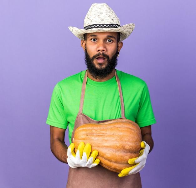 Verrast jonge tuinman afro-amerikaanse man met tuinhoed en handschoenen met pompoen