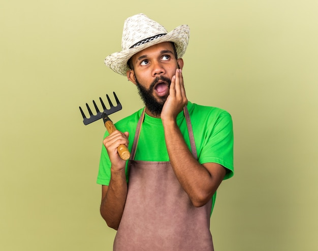 Verrast jonge tuinman afro-amerikaanse man met tuinhoed met hark hand op de wang
