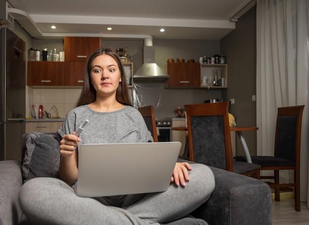 Verrast jonge vrouw en zwangerschapstest met laptop, vrouw op zoek naar informatie over zwangerschap op internet met laptop