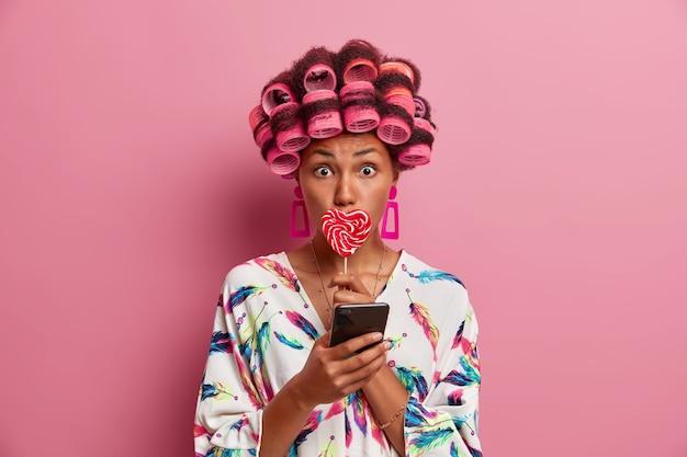 Verrast jonge vrouw gebruikt haarrollers om mooi kapsel te creëren, bedekt mond met lolly, gebruikt smartphone voor online communicatie, draagt zijden badjas, poseert tegen roze muur