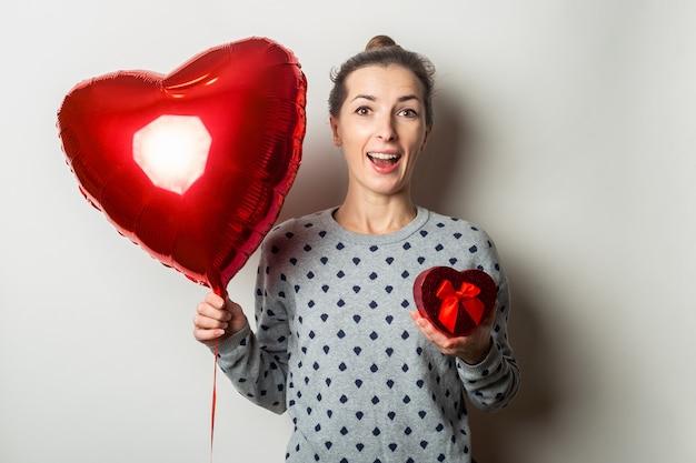Verrast jonge vrouw in een trui heeft een geschenk en een hart-luchtballon op een lichte achtergrond. valentijnsdag concept. banner.