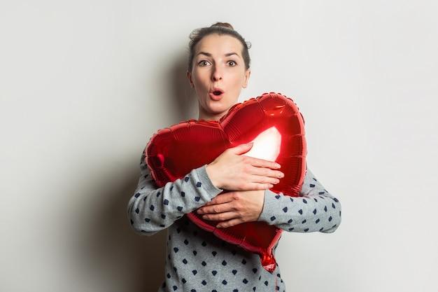 Verrast jonge vrouw in een trui koestert het hart van een luchtballon op een lichte achtergrond. valentijnsdag concept. zoek een geliefde.